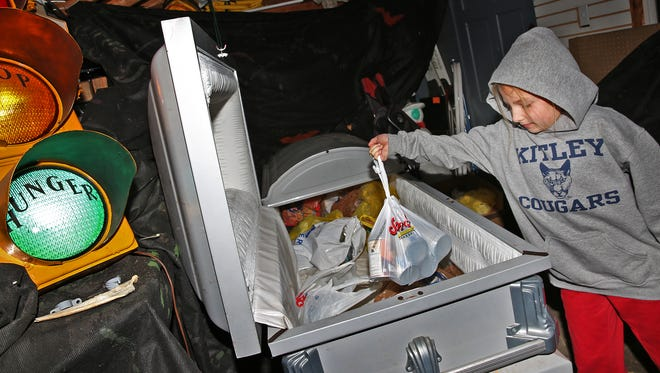 Cassidy Higgins, 8, puts a bag on donated food into a casket at the Haunt Out Hunger free neighborhood haunted house on the Southside, Saturday, October 10, 2015.  Visitors to the haunted house are asked for voluntary food donations instead of entry fees.