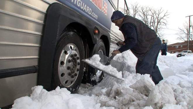 A New Jersey Transit bus driver tries to dig the rear wheels of his vehicle out after it got stuck in deep snow at 6th and Clifton Avenue in Lakewood Monday afternoon, January 25, 2016.