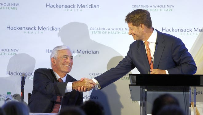 John K. Lloyd (left), Meridian president and CEO, shakes hands with Robert C. Garrett, Hackensack president and CEO, during a ceremony at the Liberty Science Center in Jersey City Tuesday, June 21, 2016, to merge their two systems and form Hackensack Meridian Health. After the merger, both of them became co-CEOs of the new system.