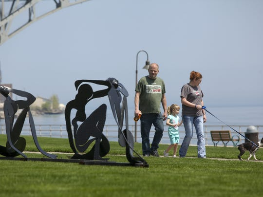Port Huron residents walk by a sculpture from a previous Port Huron Outdoor Sculpture Exhibit along the Thomas Edison Parkway.