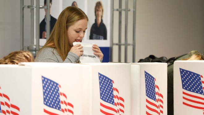 Haley Barbour seals the envelope with her ballot Tuesday, Oct. 25, 2016 as she takes advantage of early voting at Drake University in Des Moines. Barbour, a senior at Drake, took a semester off school to work with the Democratic Party in Iowa.