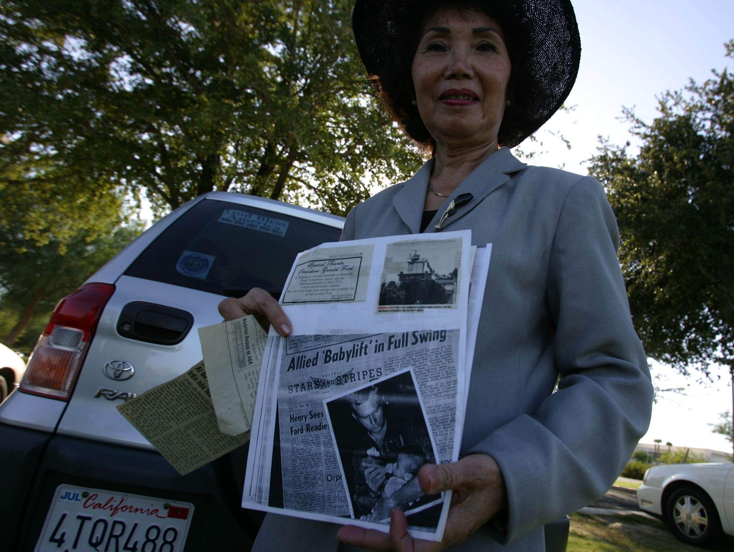 Ngan Nguyen, of Palm Desert, holds news clipping of