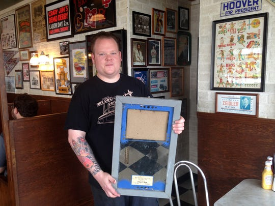 Chris Roepke, owner of the Nite Owl Drive In, holds the frame that used to display a photo of a record-setting muskie. This week, someone stole the photo from the mirrored frame, which was hanging in the restaurant's men's restroom.