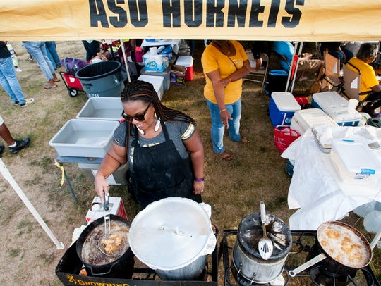 Michelle Peterson cooks while tailgating with Thomas