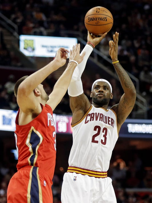 Cleveland Cavaliers' LeBron James (23) shoots over New Orleans Pelicans' Ryan Anderson in the first quarter of an NBA basketball game Monday, Nov. 10, 2014, in Cleveland. (AP Photo/Mark Duncan)
