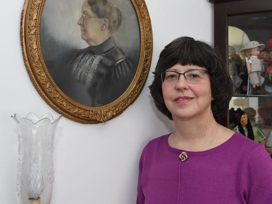 Toni Houston, standing next to a picture of her great-great-grandmother