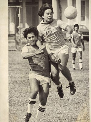Chamorro Allstars' John Calvo (12) muscles in his way past Miguel Del Valle, of SPI, to get at a high ball in a soccer game at Naval Air Station. Feb. 3, 1980.