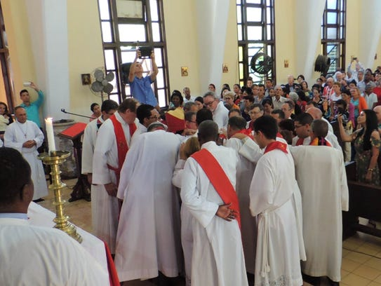 Bishop Griselda, priests and deacons lay hands on Juan