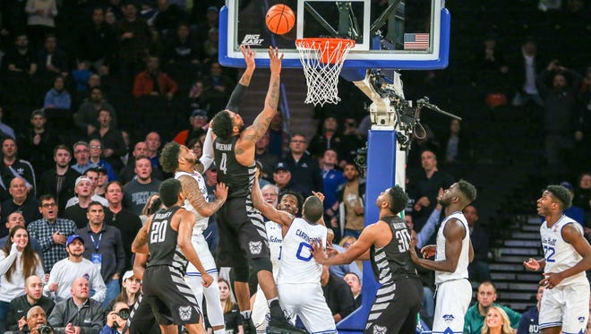Butler Bulldogs forward Tyler Wideman (4) taps in a rebound to score the game winning basket as Seton Hall Pirates guard Myles Powell (13) and guard Khadeen Carrington (0) during the second half in the Big East Tournament quarterfinals at Madison Square Garden.