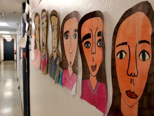Paper self portraits line a hallway at the Kradwell