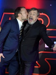Rian Johnson kisses Mark Hamill during a red carpet