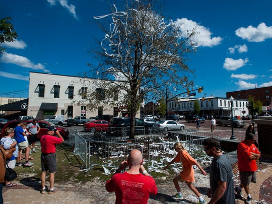 Fans gather at the oak tree at Toomer's Corner in Auburn, Ala., that was left bit charred on Sunday morning September 25, 2016 after being set on fire Saturday night after being rolled following Auburn's win over LSU.
