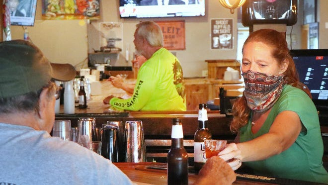 Bartender Angie Potter serves a guest while wearing a mask at the Flagler Tavern in New Smyrna Beach on Friday. Patrons can now drink while seated at bars in Florida. Bob Wargin, in the background in yellow, was one of the Tavern's regulars who returned to have a drink at the bar on Friday.