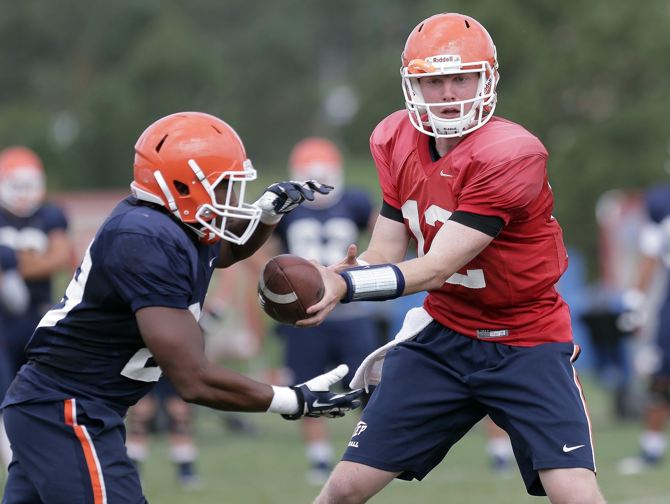 Quarterback Ryan Metz hands off to running back Aaron