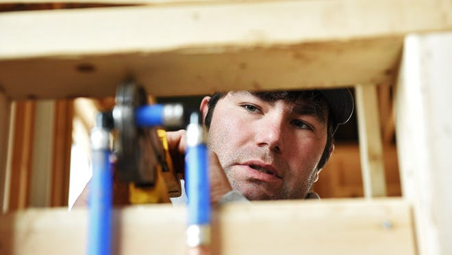 Tony Christiansen, a plumber with Frisbee Plumbing, Heating, Air Conditioning and Electrical, works at the construction site of a house Tuesday, March 22, 2016, on the east side of Sioux Falls.