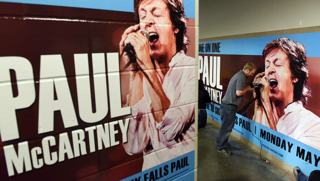 Dan Mathiowetz, with Fox Print, secures a poster welcoming Paul McCartney at the Denny Sanford Premier Center on Friday, McCartney will perform at the facility Monday night.