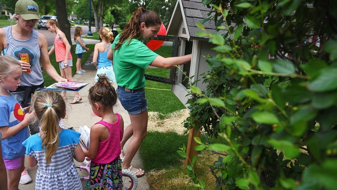 """Katie Dinsmore, 14, who lives nearby, puts a book in 9-year-old Nora Boetel's free library during a """"grand opening"""" for the free library Monday, June 13, 2016, in Sioux Falls."""