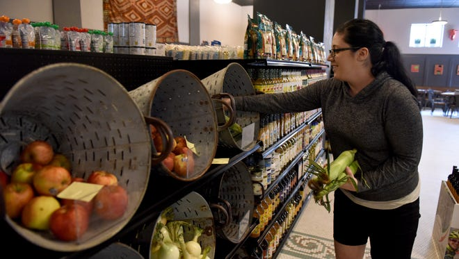 Kelly Schmidt stocks fresh corn in the produce section at Keller's Green Grocery in the Carpenter Building in downtown Sioux Falls.