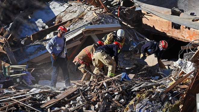 Rescue workers with Sioux Falls Fire Rescue work to rescue a third dog at the site of the Copper Lounge building collapse Sunday, Dec. 4, 2016, in downtown Sioux Falls more than 48 hours after the collapse. One person was killed and another injured in the collapse. Two other dogs were also rescued from the scene.