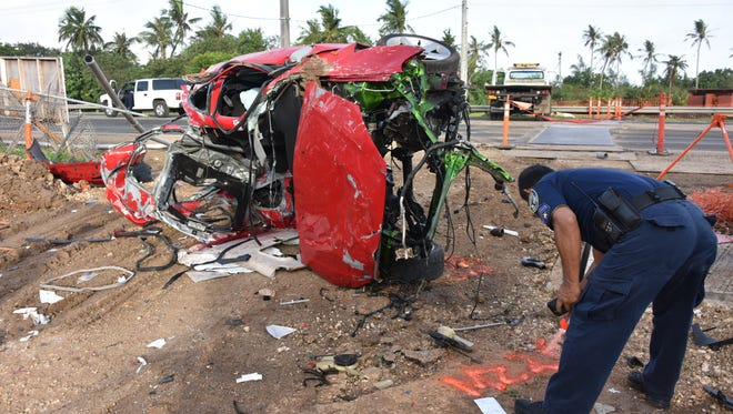 Guam Police Department Highway Patrol Division Officer James Muna marks the spot where a red Honda Acura Integra came to rest after a crash off of Route 1 in Piti early morning on Saturday, Feb. 18, 2017.