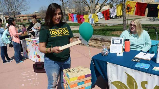 Suzie Duarte reads a giant Jenga piece at the Sexual Assault Victim Advocate Center booth during a Sexual Assault Awareness Month event on CSU's plaza on Monday, April 10, 2017. The event was hosted by CSU's Women and Gender Advocacy Center.