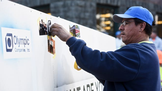 Michael Holloway, a foreman for Olympic Companies, places a photo of his family on a wall outside of the Washington Pavilion on Wednesday, Oct. 11, 2017. The wall was built by the specialty contracting business as part of a recruiting effort.
