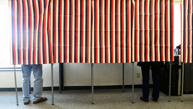Voters cast ballots behind a curtain in Port Clinton during Tuesday's general election.