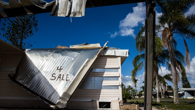 """A homeowner spray painted """"4 Sale"""" on the side of their damaged trailer at Citrus Park in Bonita Springs, Fla. on Wednesday, Dec. 6, three months after Hurricane Irma."""
