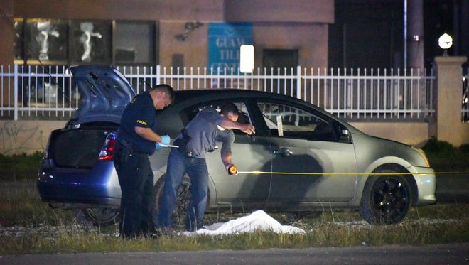 With a covered body  on the ground, police officers examine a sedan early Monday at the scene of a shooting in Harmon that left at least one person dead. The 911 call came in at 10:25 p.m. Sunday, Dec. 17, 2017, Guam Fire Department said.