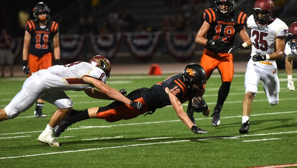 Washington High School Jhett Andersen (12) dives with