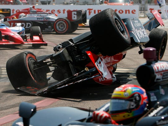 Other drivers avoid Marco Andretti's upside-down car