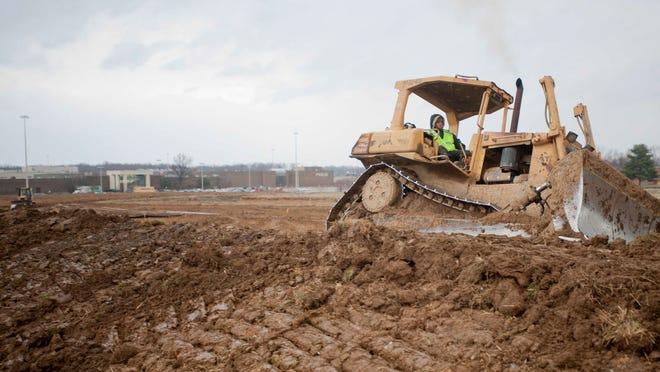 A bulldozer grades the earth in Okolona.