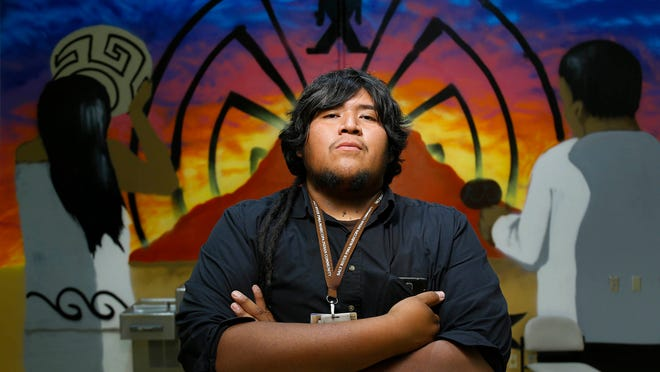 Art Teacher Dwayne Manuel stands in font of a spray paint mural that his students created Monday, April 20, 2015 at Salt River High School. The Native American artist collaborated with Nike to make a collection for the Super Bowl.