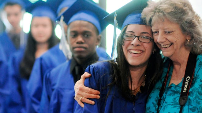 Tabernacle Christian Academy graduate Catherine Mora Brathwite, center, gets a hug from English teacher and senior class homeroom sponsor, Louise Hull, at commencement on Saturday in the City of Poughkeepsie.
