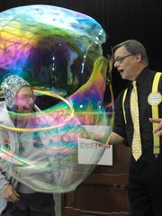 Left, Judy Metzger of Brighton is covered by a bubble made by bubbles expert Doug Rougeux of Syracuse after the announcement that Rubik's cube, Bubbles and the Little Green Army Men made it into the National Toy Hall of Fame.