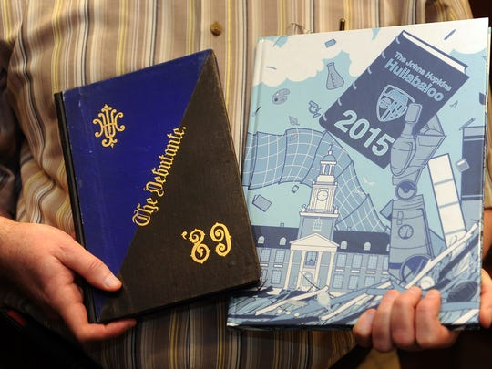 James Stimpert, senior reference archivist at the Johns Hopkins University Sheridan Libraries, holds copies of the university's first (left, from 1889) and last (right, from 2015) yearbooks. (Barbara Haddock Taylor/Baltimore Sun/TNS)