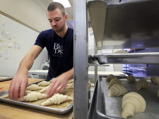 Blue Dog Bakery pastry chef Andy Wolf rolls the croissant dough into the classic shape.