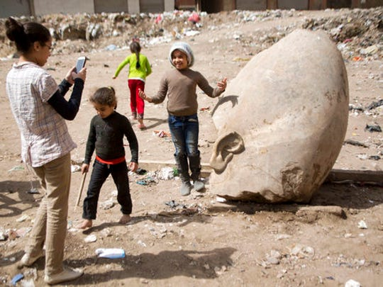 A child poses for a picture past a recently discovered statue in a Cairo slum that may be of pharaoh Ramses II, in Cairo, Egypt, Friday, March 10, 2017. Archeologists in Egypt have discovered a massive statue that may be of pharaoh Ramses II, one of the country 's most famous ancient rulers. The colossus, whose head was pulled from mud and groundwater by a bulldozer on Thursday, is around eight meters (yards) tall and was discovered by a German-Egyptian team.
