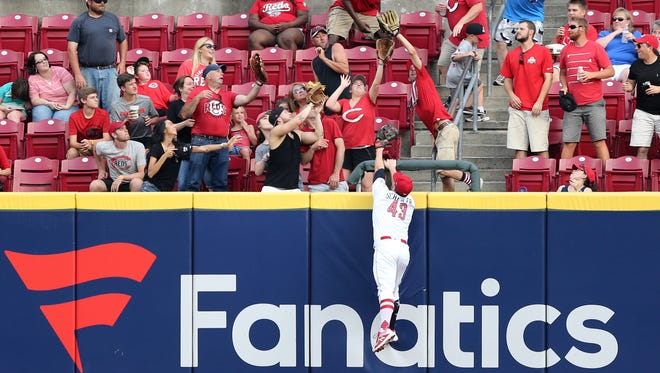 Cincinnati Reds right fielder Scott Schebler (43) leaps up for a home run ball off the bat Chicago White Sox second baseman Yoan Moncada (10) in the third inning during an interleague baseball game between the Chicago White Sox and the Cincinnati Reds, Wednesday, July 4, 2018, at Great American Ball Park in Cincinnati.