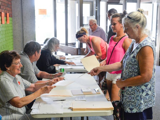 Voters line up to register and get their ballots for