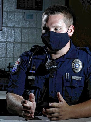 Whitehall police officer Tanner Williams wears a mask as he enters information into his computer during a traffic stop Aug. 31. Williams and other offices have had to get used to changes in their routines because of the COVID-19 coronavirus pandemic.