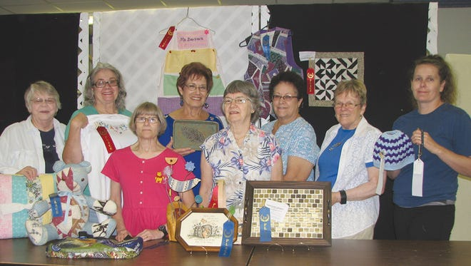 Fairview cultural arts/fashion revue winners (left to right)  Mary Alice Weber with quilted pillow and hand crafted toy; Sarah Lauricella with machine embroidery t-shirt; Barbara Comer with recycled chicken feed tote bag (on table) and story time apron (background);  Marian DePadova with pottery and pottery sculpture;  Mae Alt with counted cross stitch and basket; Winnie Decker with mosaic tray and vest (background); Marilyn Holder with quilted table topper (background); Elizabeth Keeton with crocheted messy bun hat and bracelet made by Frieda Evaskis.