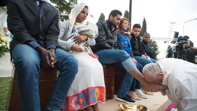 Pope Francis performs the foot-washing ritual at the Castelnuovo di Porto refugees center near Rome on March 24, 2016.