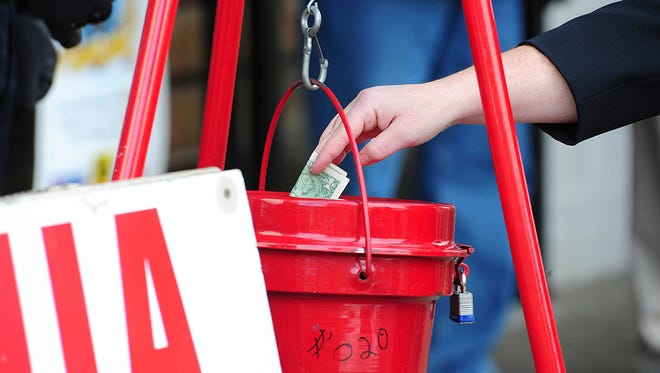 A patron donates money in a Salvation Army red kettle in Wilkes-Barre, Pa
