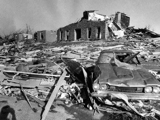 A car in foreground and a house in background are demolished on the 2300 block of Stannye Drive.   April 3, 1974