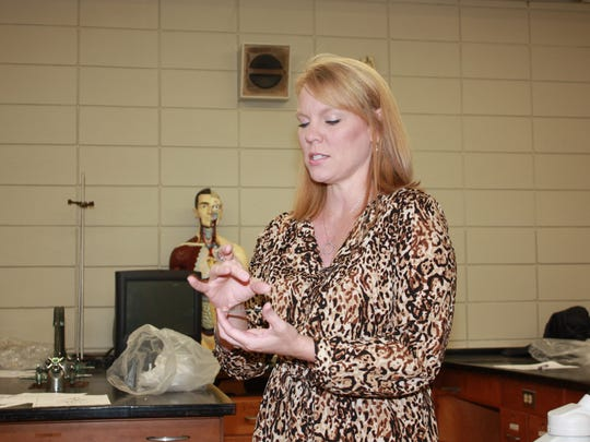 Rapides High science teacher Amy Lewis discusses slides and features of the new microscopes purchased for the school through funds from the Rotary Club of Lecompte.