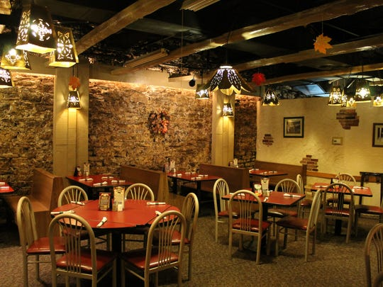 Low lighting and the rough-hewn walls create an intimate dining experience.