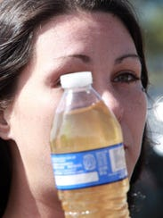 Jessica Owens of Flint, Mich., holds a bottle of drinking