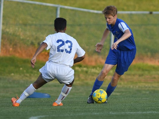 Jackson Christian's Weston Fallert (6) attempts to dribble past North Side's Mohamed Salah (23) during their game, Thursday, May 18. Jackson Christian defeated North Side, 3-2.