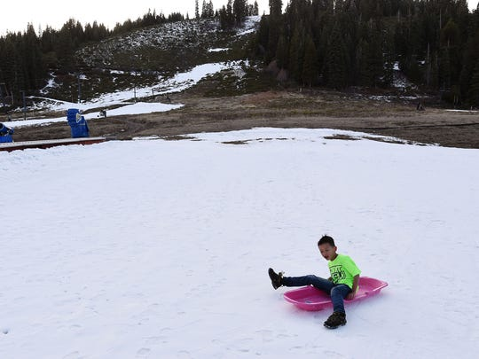 7-year-old Jiatong Cai, visiting from China, sleds down some man made snow at the base of Homewood Ski Area near Tahoe City on Feb. 10, 2015.